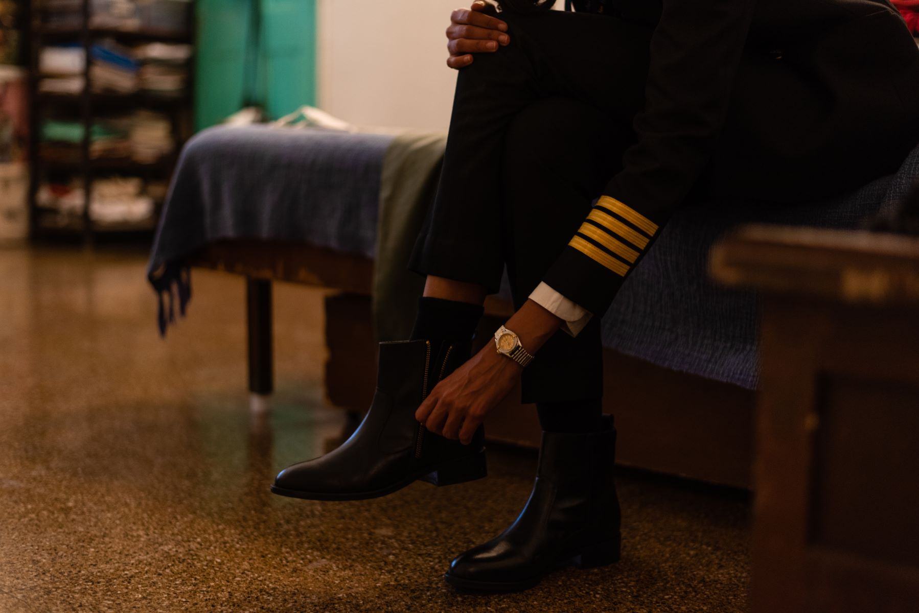 Getting dressed in uniform, Captain Thind wears her shoes in her room.