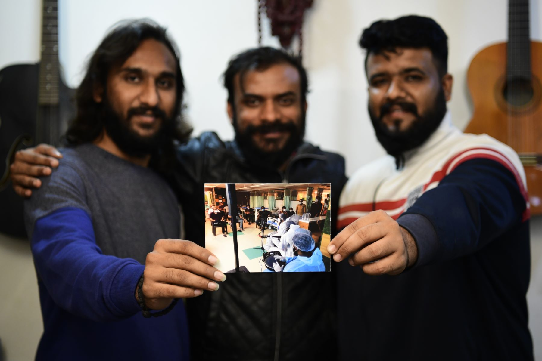 The trio poses with a photo-print reminiscing the moment of playing music for COVID-19 positive patients