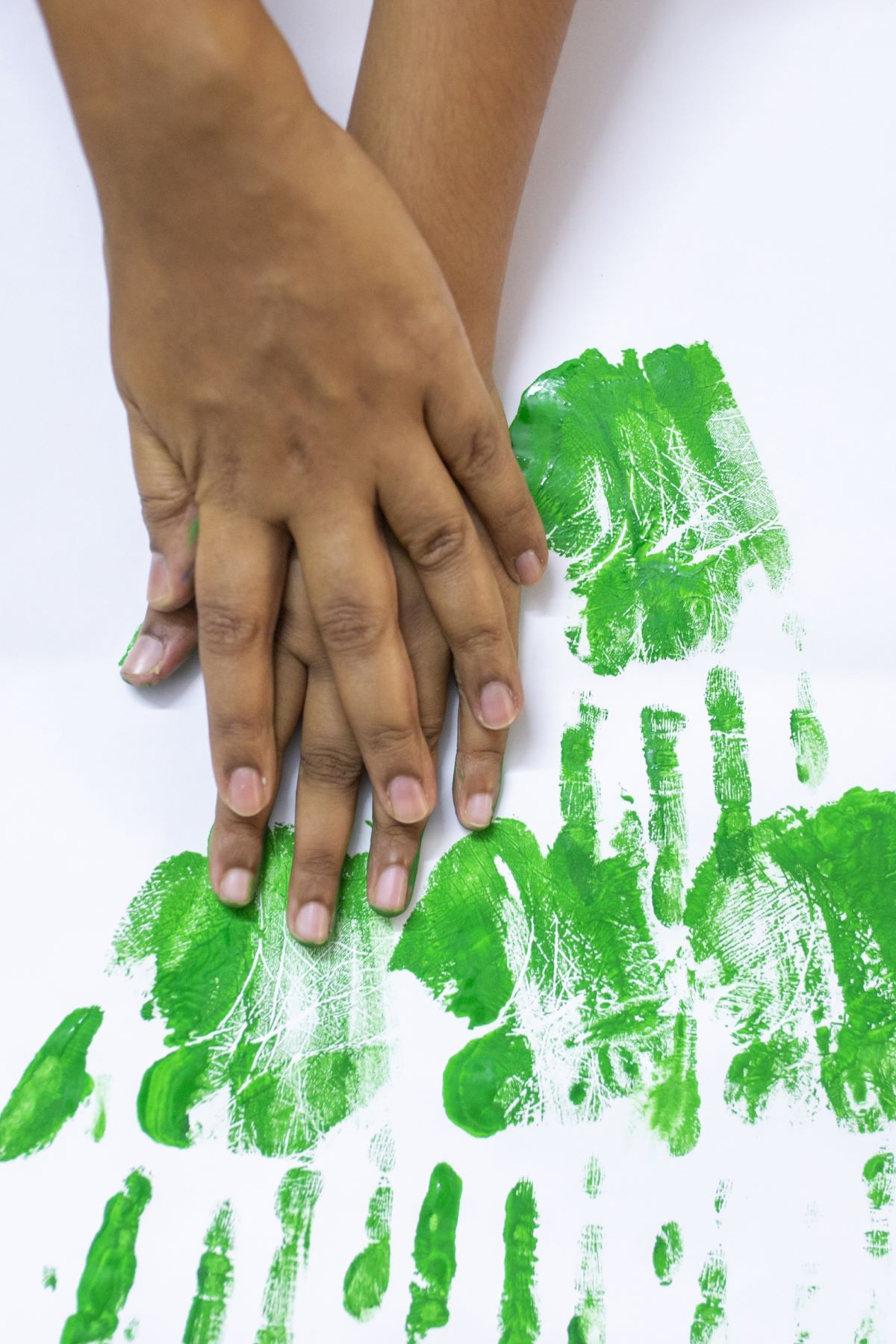 Nivrutha helping her daughter handprint on a sheet of paper to create a Christmas tree using paint on paper
