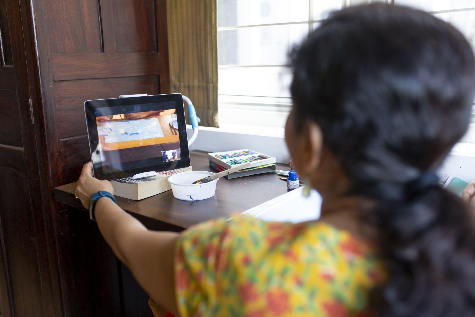Priya looking at Pavitra's painting process through her iPad