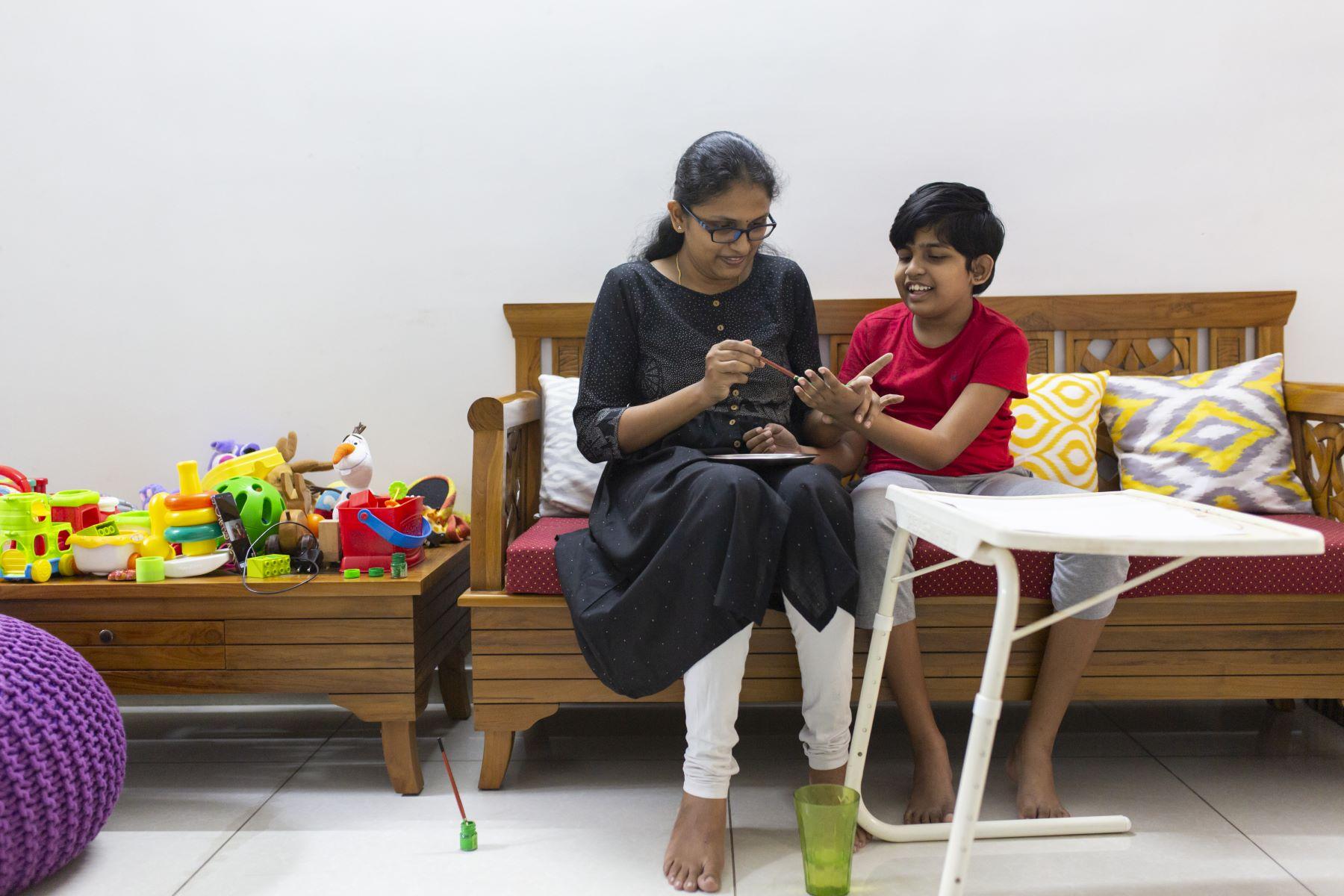 Nivrutha painting her daughter Mredini's hand
