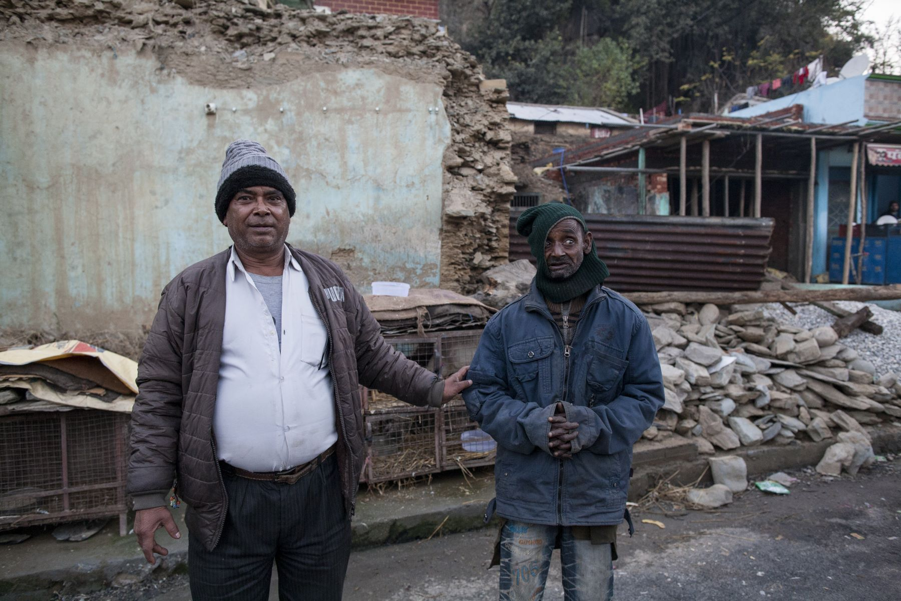 Govind Singh Chauhan ( 52) with his brother, Vijay Singh stands in front of the remains of their 30 years old hotel