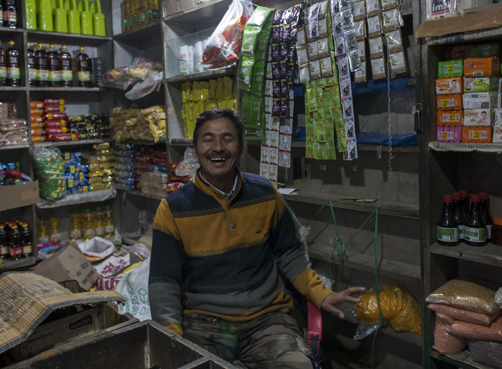 Dharam Singh Chauhan ( 45 years old ), sits at his general store in Bhallegaon