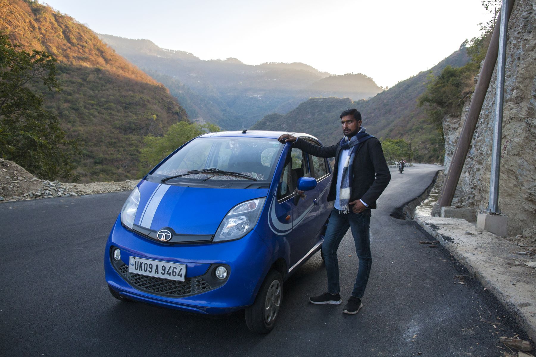 Ganesh Bhatt, a resident of the village Bhallegoan, District Tehri Garhwal stands for a portrait next to his Tata Nano car